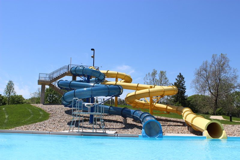 one yellow and one blue water slide opening into an empty pool