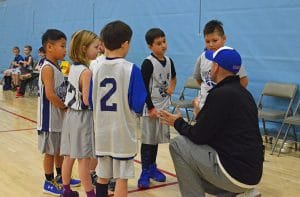 youth basketball coach leaning down in huddle during a timeout