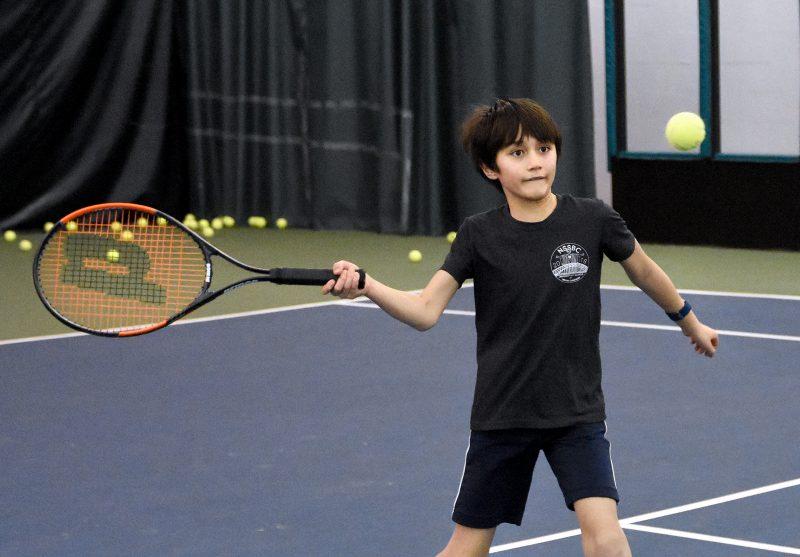 Boy swinging tennis racket towards ball in air