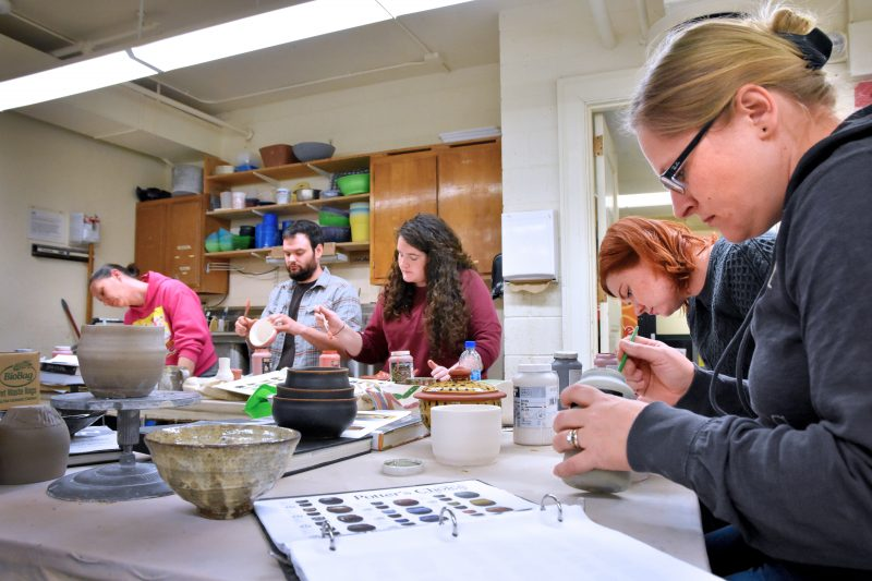 Group working on Pottery pieces in studio. Click for Pottery information