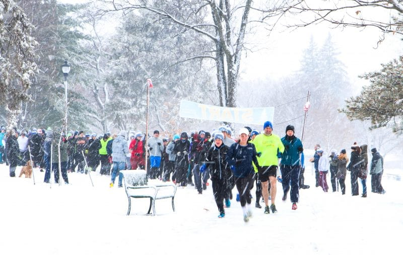 Race's starting line with racers lined up running in the snowfall