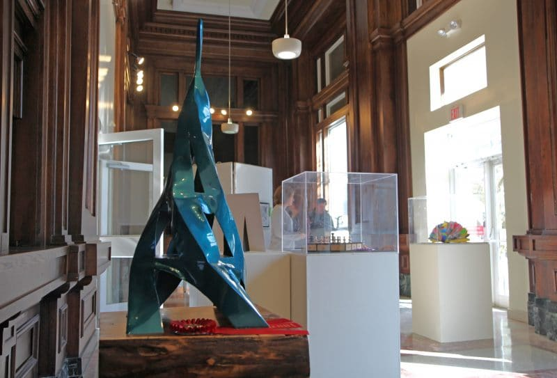 Blue twisted tower sculpture sitting on a pedestal with other sculptures in the background on display