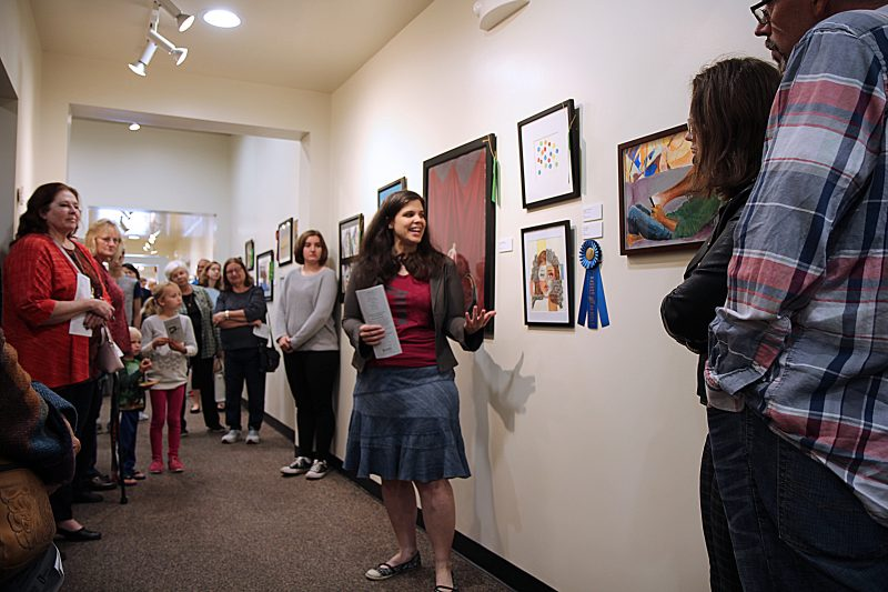 Group of artists and family members grouped around art critique explaining why she chose artwork as Best in Show.
