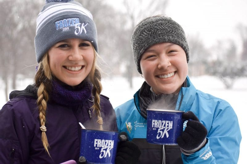 two girls smiling holding their Frozen 5K mugs