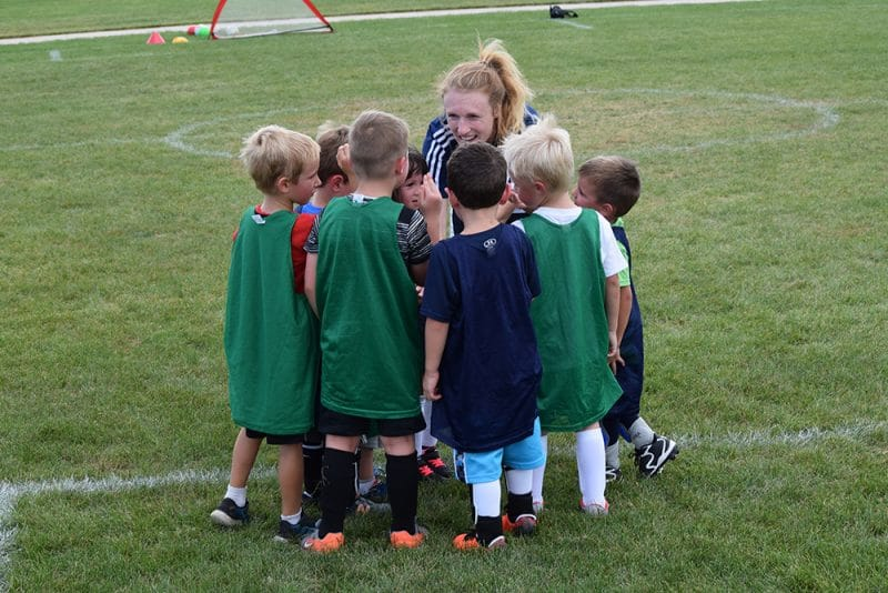 Group of youth soccer players huddled around coach giving high fives