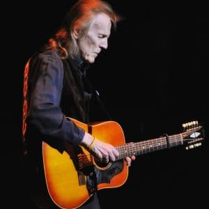 Gordon Lightfoot facing right with a sunburst acoustic guitar