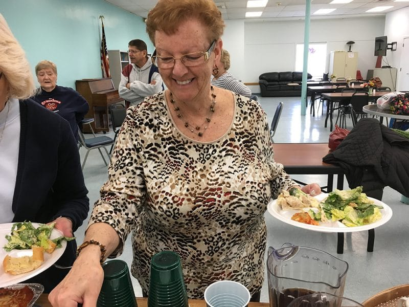 smiling older woman getting food from buffet line while smiling