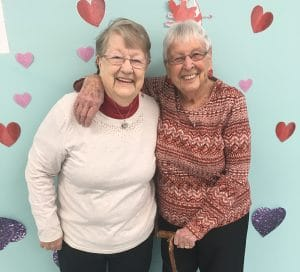 2 smiling older women standing in front of wall with hearts.