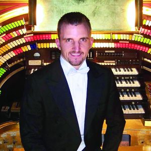 man standing in front of Organ with 4 rows of piano keys and hundreds of brightly colored switches