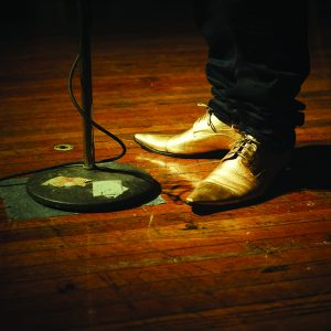 shiny gold shoes standing on worn hardwood floors with microphone stand.