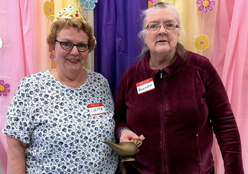 "2 older ladies smiling with a crown and ""magic lamp"""