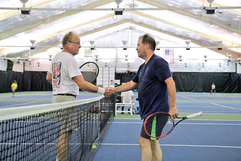 2 older men in the middle of tennis court on either side of net shaking hands at the end of the match