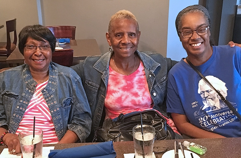 3 older ladies sitting at a table smiling