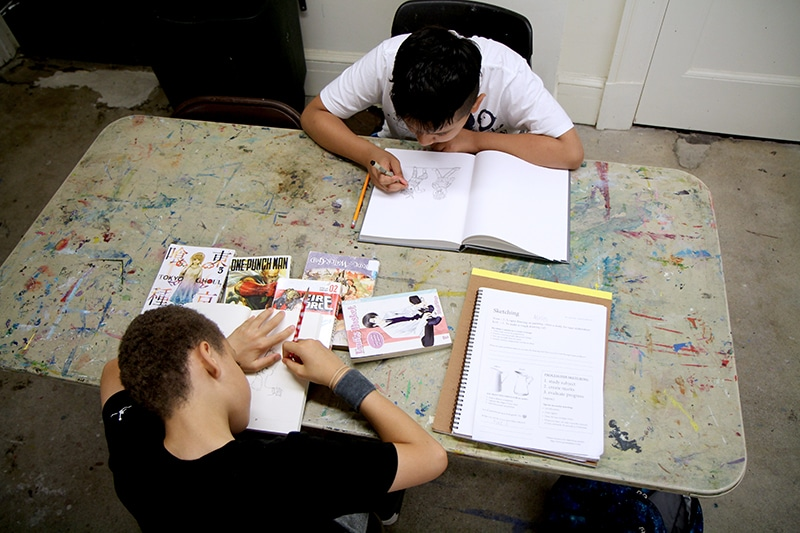 two boys sitting across from one another drawing with sketch pads and manga books.