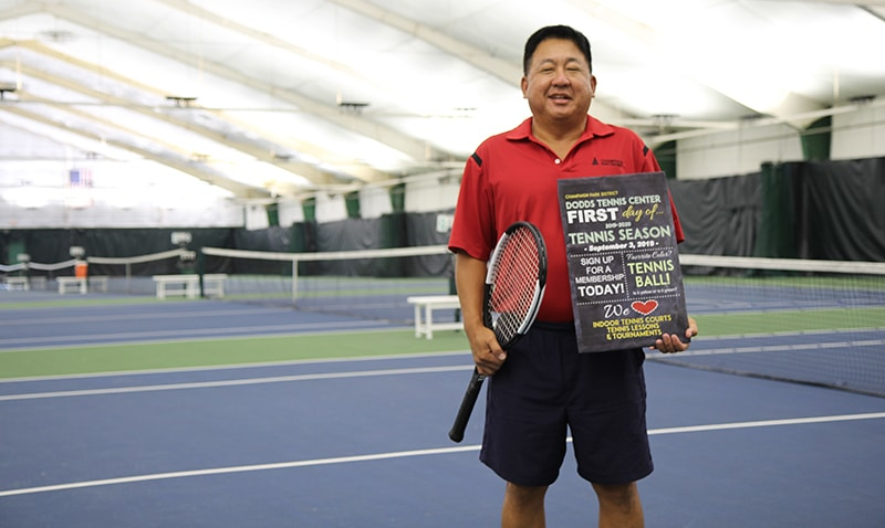 Yuri Sohn standing in front of indoor tennis courts holding a tennis racket and sign that says: Dodds Tennis Center First Day of Tennis Season.