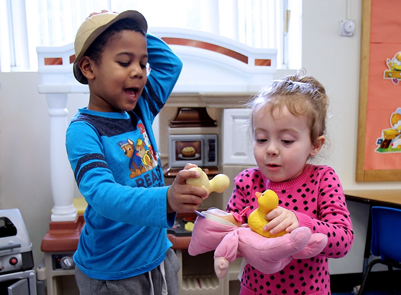 a young boy and young girl playing pretend with rubber duckies and a baby doll