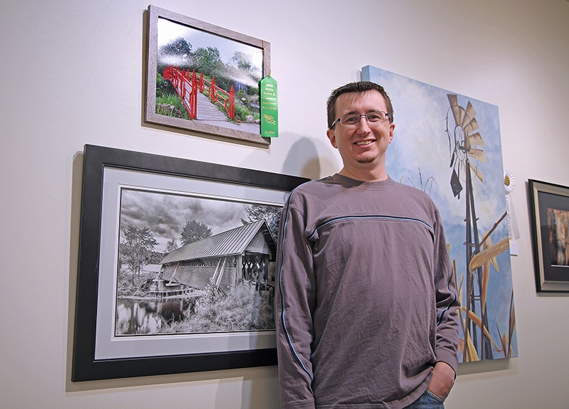 Man proudly standing in front of framed artwork on the wall.