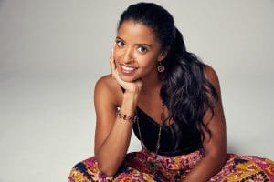 Renee Elise Goldsberry in front of grey backdrop, sitting, smiling with elbow on knee