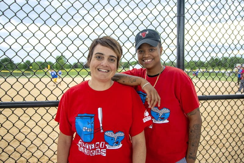 2 women standing in front of baseball diamond with team shirts on: The Cereal Killers.