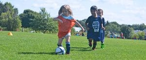 little girl in orange jersey running down the soccer field kicking a soccer ball with 2 boys in dark blue jerseys chasing her down.