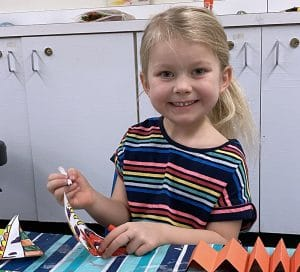 Young girl sitting at table smiling straight to the camera while coloring fish paper lantern she is making.
