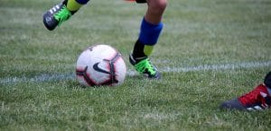 close shot of Nike Soccer ball being kicked by youth soccer player with black cleats, green laces, and blue shin guards.