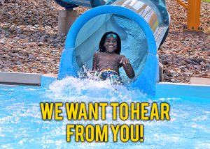 Boy making a big splash at the end of a water slide. Text reads: We Want to hear from you!