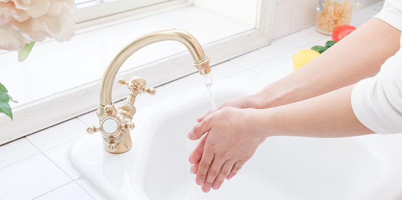 Hand washing sink in the hands of a woman by the window