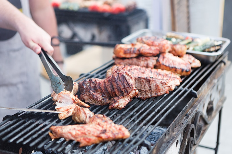Male chef cooking pork ribs on grill at BBQ party. Roasted meat with crispy crust and sauce, closeup