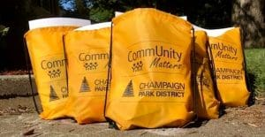 5 orange drawstring bags with black CommUnity Matters and Champaign Park District logos. They are positioned with one in the front and two rows of two in a pyramid fashion.