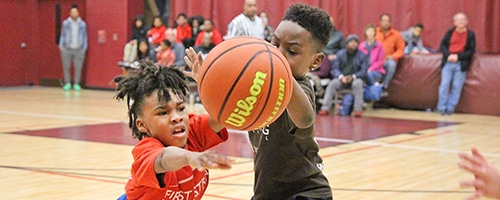 Boy passes basketball with difficulty while defender is close with arms extended.