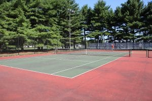 Outdoor tennis court surrounded by giant pine trees.